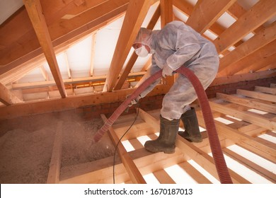 Worker with a hose is spraying ecowool insulation in the attic of a house. Insulation of the attic or floor in the house