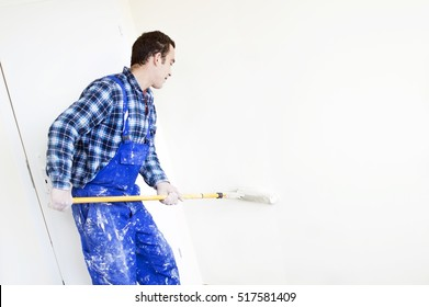 Worker house painter paints a wall in the background a bright room