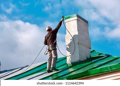 Worker of Industrial Alpinist Services  painting chimney on the roof with paint spray gun.  Professional climber wearing uniform, helmet and using safety harness. Risky job. Extreme occupation.