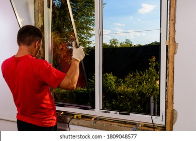 The worker inserts glass into the window frame, triple glazing of the plastic window, insulation and insulation.