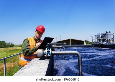 Worker inspecting valve for filtering water. Focus on Valve.