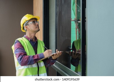 Worker, inspector, engineer is checking building structure around window with checklist in hand. Inspect and checking concept