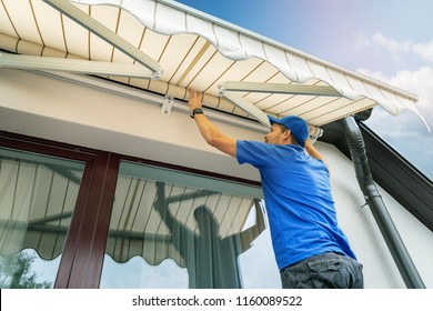 worker install an awning on the house wall over the terrace window