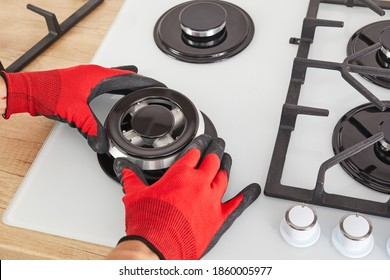 Worker install burner on gas hob in kitchen interior. Repairs of gas control panel.