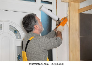 Worker install door, using polyurethane foam to fix it at wall