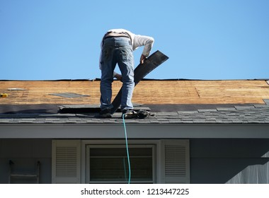 worker install new shingle on the roof of the house for roof repair