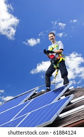 Worker installing alternative energy photovoltaic solar panels on roof