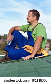 Worker installing bitumen shingles - taking a break sitting on the roof