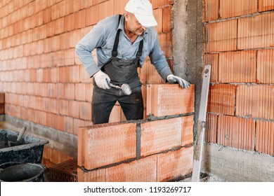 Worker installing bricks with mortar and rubber hammer. Construction industry details