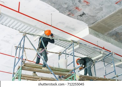 Worker installing cable tray with electrical wiring arrange on ceiling at offshore platform.