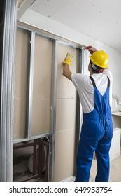 Worker Installing Drywalls