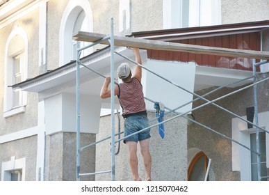 Worker installing house fascia boards and soffit outdoors