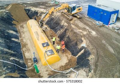 Worker installing a huge fuel tank