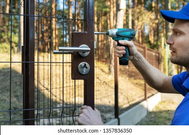 worker installing the lock for new metal fence gates