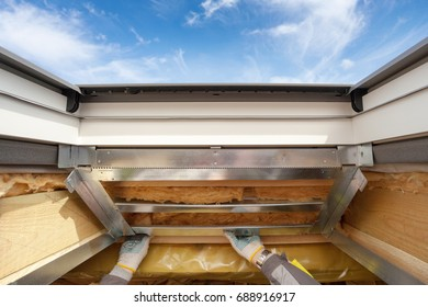 Worker installing metal frames on attic with Plastic (mansard) or skylight window and environmentally friendly and energy efficient thermal insulation rockwool.