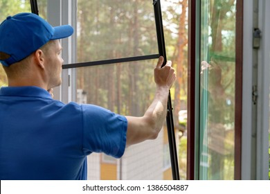 worker installing mosquito net wire mesh in plastic window frame
