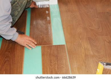 worker installing new laminate flooring
