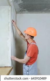Worker is installing a perforated aluminum corner to an external the angle.