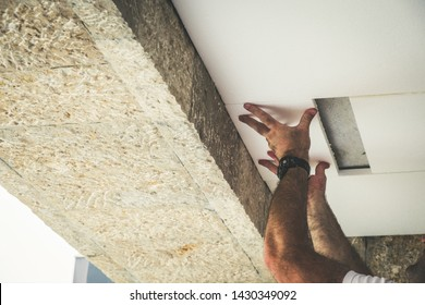 Worker installing polystyrene insulation boards