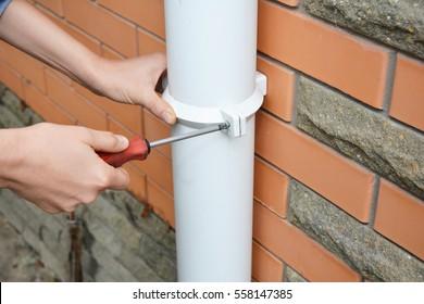 Worker Installing rain gutter downspout pipe. Contractor hands repair rain gutter  downspout pipe with screwdriver. Guttering, Gutters, Plastic Guttering & Drainage. Guttering Down pipe Fittings