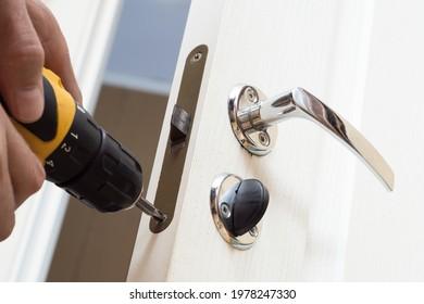 Worker installing or repairing new lock and door knob with screwdriver. Locksmith repair or install the door lock in house.