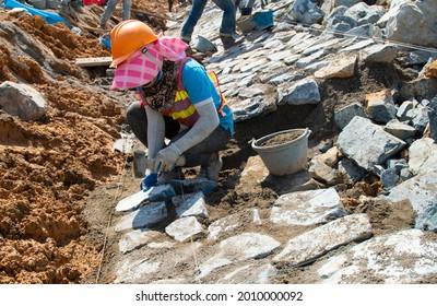 Worker installing riprap slope protection in a road construction project. Road slope protection from landslides, and floods.