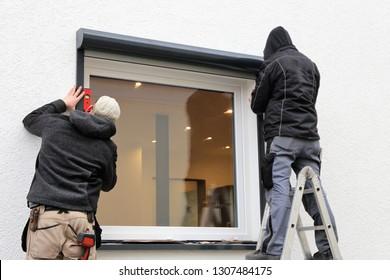 Worker installing a roller shutter
