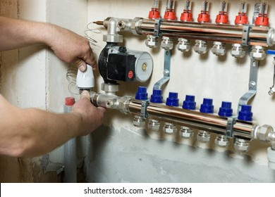 A worker is installing a thermal head on the home heating system distributor.