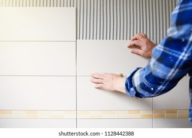 Worker installing tiles on wall