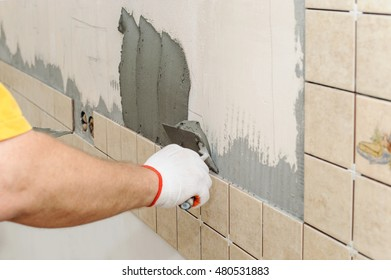 Worker installing tiles on the wall in the kitchen. He put adhesive using a trowel.