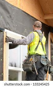 Worker installing trim around a window prior to putting on siding at a large commercial housing development in Oregon