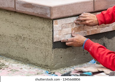 Worker Installing Wall Tile at Construction Site.