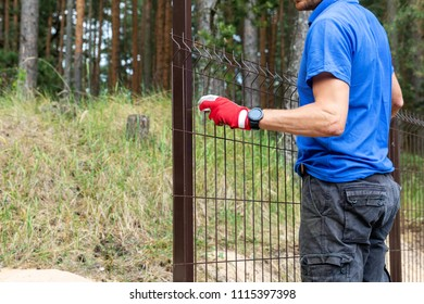 worker installing welded metal mesh fence
