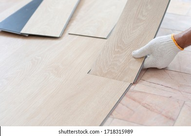 Worker installing wood plank for new room. Home renovation with vinyl wood floor Installation for home decoration with laminate vinyl wood floor.