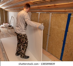 Worker installs drywall on the walls in the room.