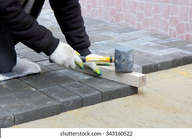 Worker installs paving slabs in the courtyard