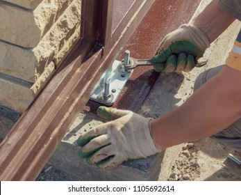 The worker installs rollers on the sliding gate