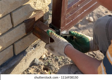 The worker installs rollers on the sliding gate .