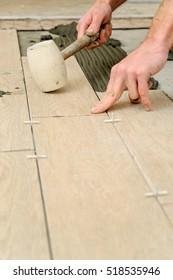 Worker installs tiles on the floor. He knocks a rubber mallet.