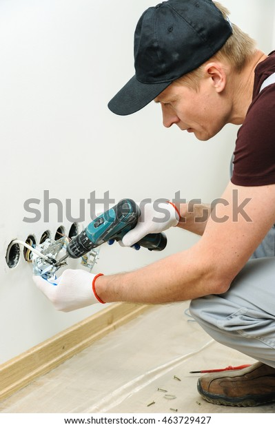 Worker installs a TV wall socket using a screwdriver.