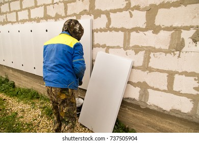 The worker insulates the house from foam plastic