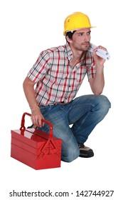 Worker kneeling by his tool kit