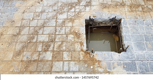 Worker or labor digging hole for installation pillar or pole on cement ground with copy space at construction site and no strict and make symbol to tell danger area- Unsafe, Safety and structure