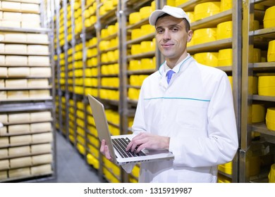 worker with a laptop in his hands at the cheese warehouse