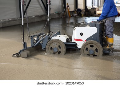 Worker with laser screed machine leveling fresh poured concrete surface on a construction site