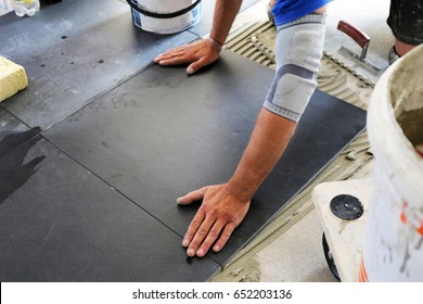 Worker laying floor tiles