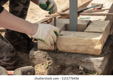 The worker lays bricks on the construction site .