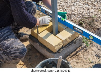 The worker lays bricks on the construction site