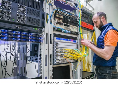 Worker lays telecommunication cables in the server room. A man twists the wires in a modern data center. A technician connects Internet backbones with a central router.