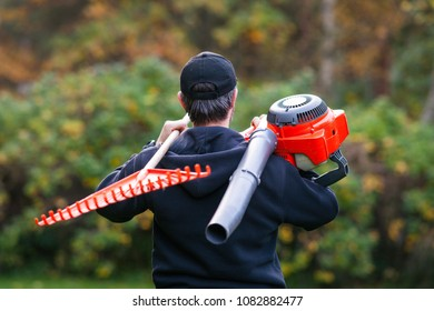 Worker with leaf blower and rake